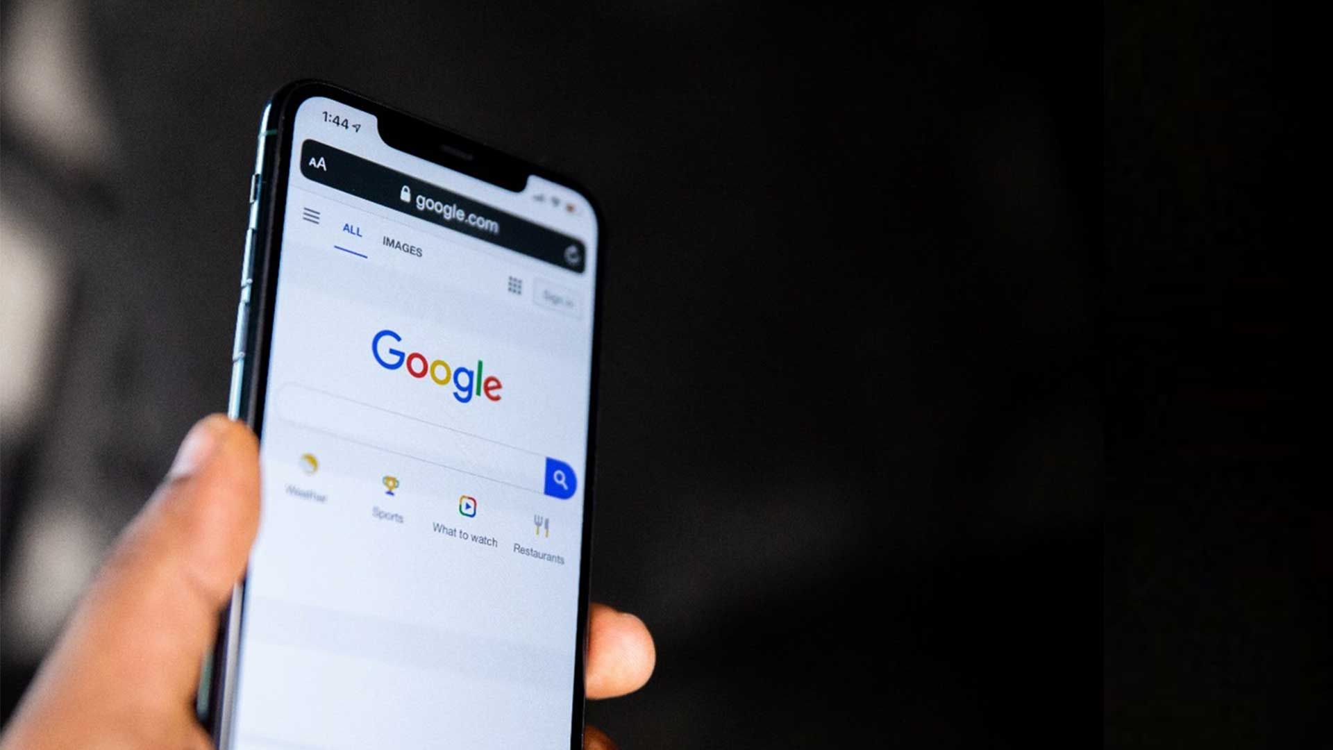 A person holding up a phone with the Google homepage on it.